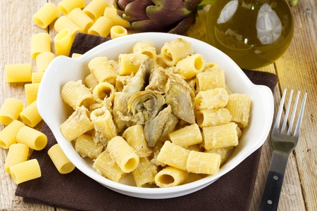 recipe decorated: Dish of pasta with artichoke. Traditional Italian recipe. Served in a white terrine and decorated with fresh artichoke, olive oil and raw pasta