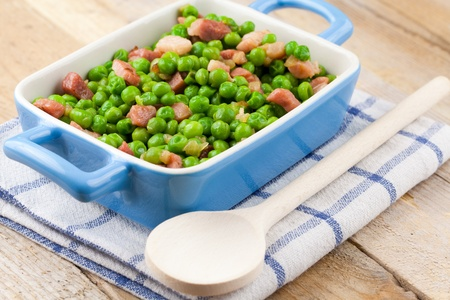Terrine of peas cooked with bacon and ham over a rustic napkin and a wooden table Stock Photo - 12551887