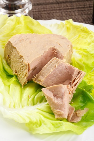 Chunk of tuna fish in a lettuce bed, served in an elegant place setting photo