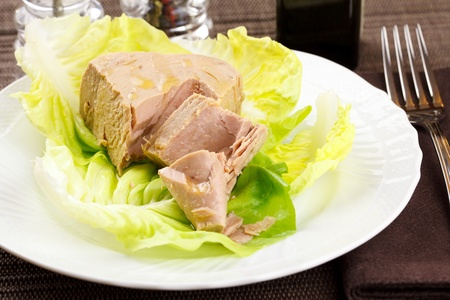 Chunk of tuna fish in a lettuce bed, served in an elegant place setting