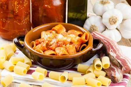 Traditional Italian recipe pasta Amatriciana  Macaroni with tomato and bacon sauce topped with parmesan cheese