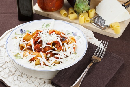 Traditional recipe from Sicily, Italy, pasta Norma  Macaroni with tomato and eggplant sauce topped with freshly grated ricotta cheese  Raw ingredients in background Stock Photo - 12552055
