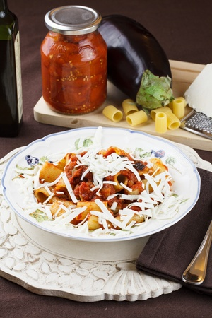 Traditional recipe from Sicily, Italy, pasta Norma  Macaroni with tomato and eggplant sauce topped with freshly grated ricotta cheese  Raw ingredients in background Stock Photo - 12551978