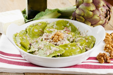 Green ravioli pasta filled with fresh ricotta cheese and artichoke  Topped with cheese and nuts cream photo