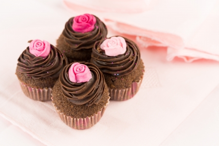 Group of delicious chocolate cupcakes decorated with red and pink roses over a pink tablecloth
