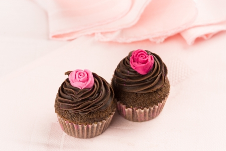 Two chocolate cupcakes decorated wit red and pink roses over a pink tablecloth