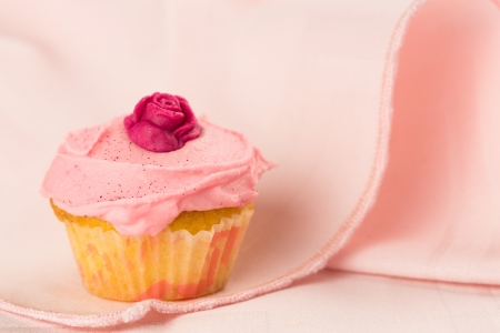 Pink cupcake decorated with red rose over a pink tablecloth Stock Photo
