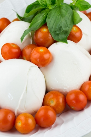 Dish full of Italian fresh  mozzarella cheese balls and cherry tomatoes decorated with basil leaves Stock Photo