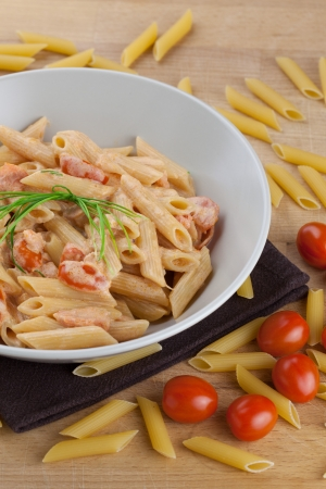 Pasta with salmon and cherry tomatoes, garnished with fresh bunch of chives and surrounded by raw ingredients Stock Photo