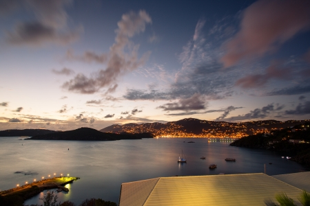 View of Charlotte Amalie, St  Thomas at dusk with boats in the bay and lighted dock and houses
