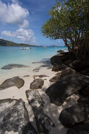View of Magens Bay in St Thomas, USVI, in a summer day with boats on the sea and rocks on the sand Stock Photo