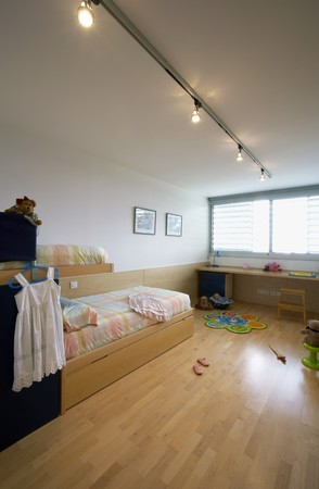 Girls spacious bedroom with bed in built wooden desk and wooden floor