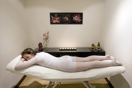 massage table: Woman lying on a massage table in a health spa