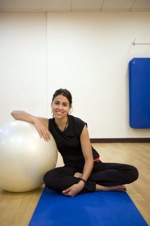 Woman holding a fitness ball and smiling photo