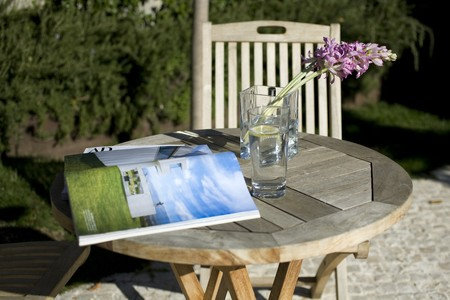 noone: Book with a glass of water on a table in a garden