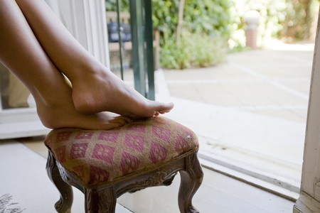 footstool: Close-up of a womans legs on a footstool