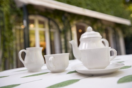 Tea cups with a tea kettle on a table in a garden