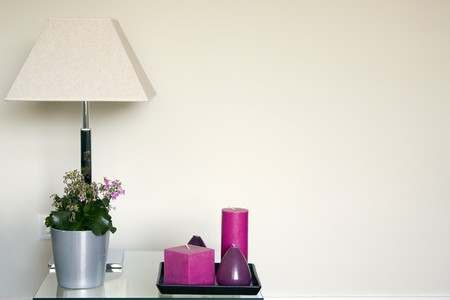 Lampshade with a houseplant and candles on a sideboard
