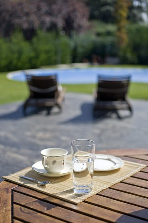 Tea cup with a glass of water on a table in a garden photo