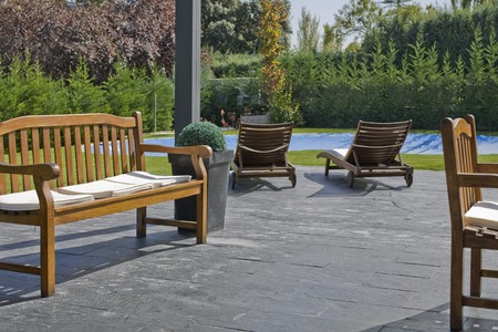 Bench with lounge chairs at the poolside Stock Photo