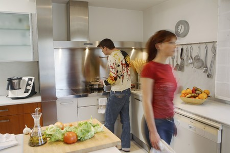mediterranian style: Young couple cooking in kitchen LANG_EVOIMAGES