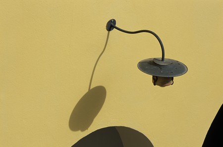 mediterranian style: View of a lamp on a yellow wall