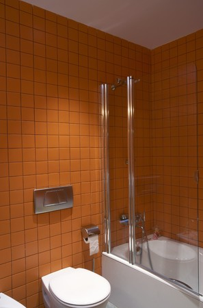 spanish tile: Bathroom with brown tile wall commode and glass partition