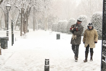 Couple walking on a snow covered road, Madrid, Spain photo