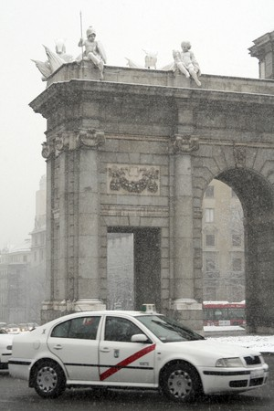Traffic near a monument during rain, Puerta De Alcala, Alcala Gate, Madrid, Spain photo