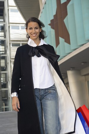 streetlife: Young woman smiling dressed with bluejeans and black cloak walking by the Sports Palace in Madrid, Madrid, Spain Stock Photo