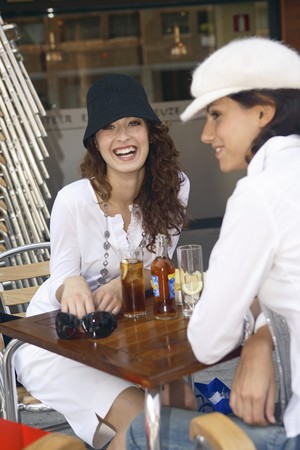 designer labels: Two young women sat in a terrace talking and drinking.