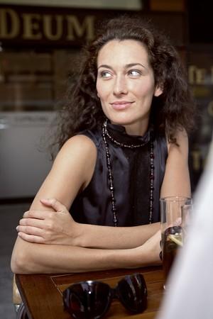 attractiveness: Joven mujer latina con pelo oscuro tiempo rizado sonriendo y mirando hacia el lado