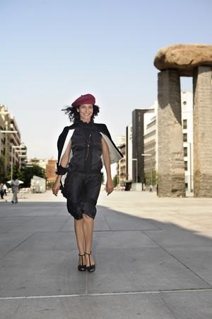streetlife: Young model dressed in black walking in Avenue of Felipe II, Madrid, Spain Stock Photo