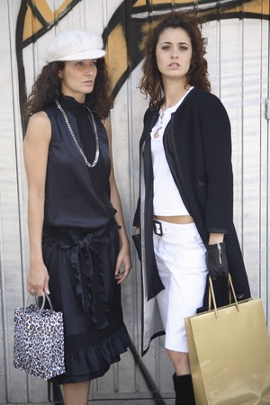 designer labels: Two young women models dressed in black and white possing for a picture in front of graffiti