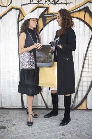 designer labels: Two young latin women models dressed in black and white talking in front of graffiti after going shopping.