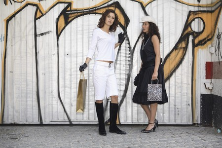 Two young latin women models dressed in black and white talking in front of graffiti after going shopping. photo
