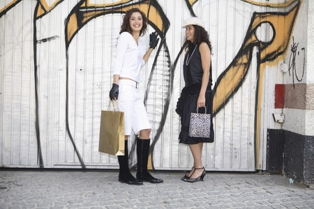 streetlife: Two young latin women models dressed in black and white talking in front of graffiti after going shopping.