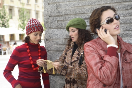 designer labels: Young latin woman talking on th mobile phone while other two friends chat in the back.