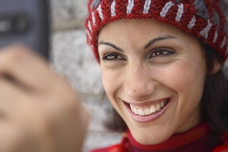 Young latin woman taking a picture of herself on her mobile phone. Stock Photo - 7475722