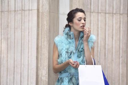 streetlife: Young woman doing her makeup