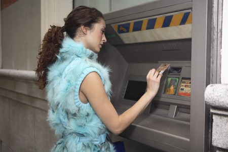 cashpoint: Young latin woman at ATM Stock Photo