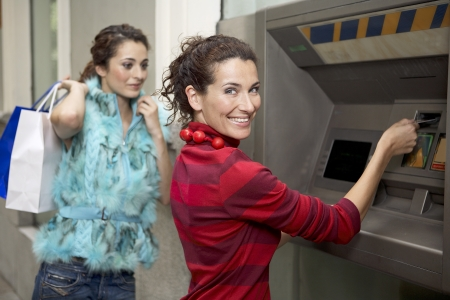 cashpoint: Two young latin woman at ATM before going shopping Stock Photo
