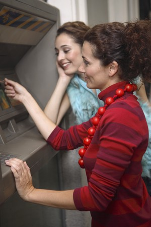 outside machines: Two young latin woman at ATM before going shopping Stock Photo