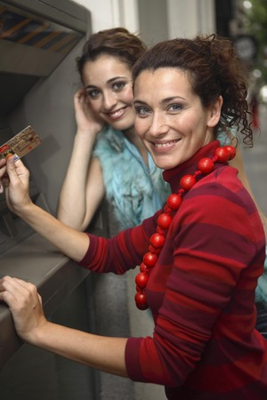 attractiveness: Dos Latina joven en cajero autom�tico antes de ir de compras  Foto de archivo