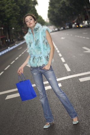 designer labels: Youn latin woman crossing the street Serrano, Madrid, Spain