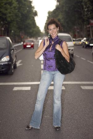 streetlife: Youn latin woman crossing the street Serrano, Madrid, Spain