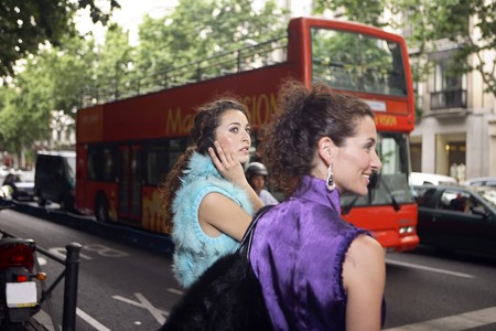 Two young latin women crossing the street Serrano in front of Turistic bus, Spain photo