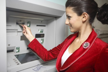 automatic teller machine: Young woman dressed in red, at ATM with credit card. Stock Photo