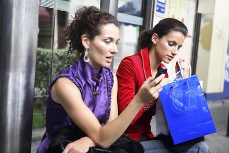 mobiele telefoons: Twee jonge latin vrouwen op een bus stoppen, praten.