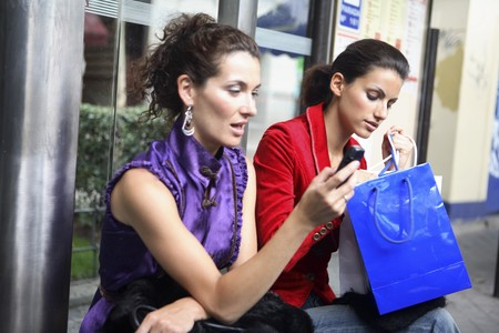 Two young latin women at a bus stop, talking.